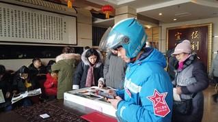 春节期间前来店里取餐的外卖小哥,为了方便网上叫餐的顾客,店里跟饿了么等APP合作,设置了专门的外卖取餐点。(杨波 摄)