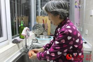 叶先生的母亲用自来水洗苹果 张静淇/摄