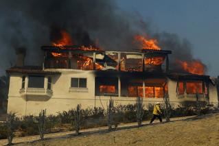 12月5日,在美国加利福尼亚州南部文图拉县,消防员经过一处着火房屋。新华社/路透