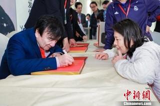 杨绍明在新书上签名 主办方供图 摄