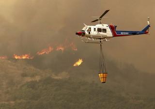 12月5日,在美国加利福尼亚州南部文图拉县,一架直升机参与灭火。新华社/美联