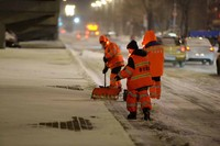 2月19日夜,环卫工人在哈尔滨市区一条主干道上进行清雪作业。