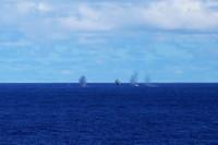 """2月19日,在海上现场反击演练中,海口舰主炮射击的炮弹落在靶标范围内,实现对""""敌舰""""的摧毁打击。新华社记者曾涛摄"""