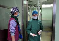 3月22日,河南省人民医院心血管内科四病区主任医师陈岩(右)在进行了将近3个小时的手术后走出导管室。