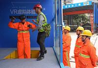 3月22日,在重庆轨道交通九号线3标项目部,工人李锦松(左一)在安全员的帮助下体验高空坠落游戏。