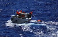 """4月27日,在西太平洋海域,中国海军远航访问编队进行海上联合搜救训练时,一艘小艇成功打捞""""落水者""""。新华社发(禹威摄)"""