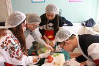 """竞赛现场戴着帽子和手套的""""大厨们""""正热火朝天地做着俄式沙拉(人民网记者 华迪 摄)"""