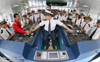 """6月23日,在烟台打捞局""""德淇""""轮驾驶室,航海专业学员们学习船舶操控台的使用。唐克/人民图片"""