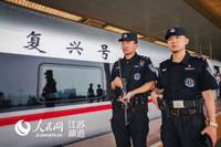"""图为""""复兴号""""高铁列车停靠南京时,特警开展武装巡逻"""