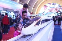 """10月16日,家长带着孩子在北京举行的""""砥砺奋进的五年""""大型成就展上观看""""复兴号""""动车组列车模型。"""