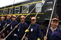 """列车""""洗澡工""""们手拿几米长的竹竿鬃毛刷,愉快地开始了一天的工作。"""