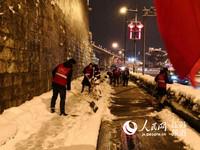 图为南京市民参与到扫雪行动之中。