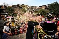 """西江苗寨春节期间的民俗欢庆活动,图为村民扛幸福""""鸡仔仔粑""""。"""