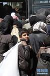 3月16日,在叙利亚首都大马士革以东胡什纳斯里地区的一处临时安置点,一名叙利亚男孩背着行李准备上大巴车。