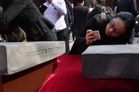 4月16日,一名女士在捐赠仪式上拍摄金砖。