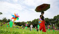 6月17日,家长带孩子在三亚南山景区的风车景观中游览。