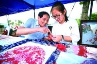 浦江剪纸国家级代表性传承人吴善增(左)指点学生蒋璇芝剪纸技法。