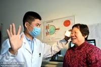 10月14日,在临沂市郯城县马头镇卫生院,眼科医生为做完白内障手术的袁金英老人揭去纱布。