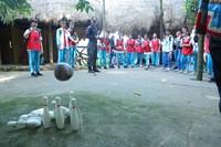 """同学们体验黎族传统民俗竞技""""椰子保龄球"""