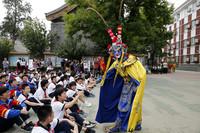 5月14日,民间艺人在为中学生表演川剧变脸。