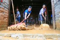 6月22日,江西省吉安市峡江县桐林乡党员干部正在帮助村民清理积水。