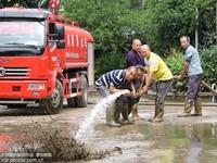 6月23日,四川省达州市大竹县基层党员干部在永胜镇敬老院清理洪水退落后的淤泥。
