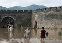 """8月11日,临海老城居民从仍有积水的""""兴善门""""门前经过。"""