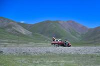 8月9日,在青海省玉树藏族自治州治多县治渠乡境内的一处海拔4200余米的电网建设工地上,工人从远处运送用于混凝土搅拌的水。
