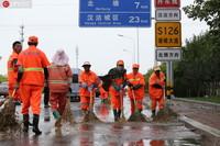8月12日,天津市滨海新区港城大道,公路养护人员正在清理道路积水。