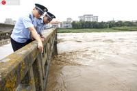 8月16日,吉林图们口岸,两名边检民警实时查看图们江水位和流速变化。