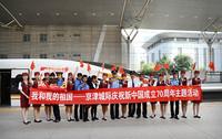 9月27日,身着新制服的京津城际乘务组与旅客在天津站站台上合影留念。(人民网 张玫 摄)