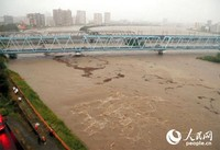 12日,受19号大型台风影响,多摩川区域水量激增,消防、警察实施戒备。图片右侧河岸部分平时为棒球练习场,河水暴涨时已全部淹没。而桥上平时会有京急线、JR线通过,也因河水暴涨而封闭。(图片来源:日本《朝日新闻》网站)