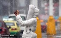 11月8日,新疆乌鲁木齐市市民冒雪出行。