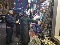 1月1日,城管队员围在街区一处水果店前,敦促店主收拾门前占道的甘蔗皮,以免影响人群疏散。 新华社记者 王昕怡 摄
