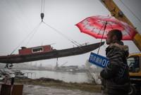 在长江新螺段白鱀豚国家级自然保护区渔船拆解现场,长江捕捞村渔民夏明星注视着被吊起的渔船,他手上的渔船编号牌也即将被收回(2019年12月25日摄)。