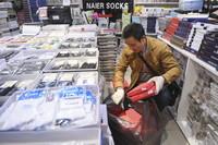 冉光辉在重庆朝天门大正商场内整理即将搬运的货物(1月5日摄)。