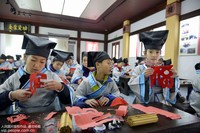 1月13日,浙江省舟山市定海区环南街道少年冬令营学子在体验民俗剪纸。