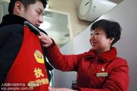 2020年1月21日,临汾西站(山西),临汾铁路公安处民警李永浩上岗前,母亲陈海涛为其整理警容风纪。