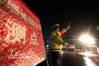2月5日晚,运城市公安局盐湖公安分局交警大队民警冒着鹅毛大雪在运临路疫情防控点严密排查车辆和群众。