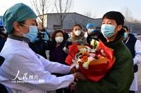 2月7日,在河北省唐山市传染病医院,医护人员向唐山市首批治愈患者送花表示祝贺。