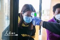 2月12日,在贵州省毕节市大方县雨冲乡金门陶瓷园区,工作人员正在对返岗员工进行体温测量。