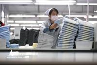 2020年2月14日,在位于山东青岛市即墨区的青岛即发集团有限公司生产车间里,工人在包装出口到海外的服装配资 。