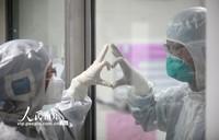 2月14日,在扬州市第三人民医院新冠肺炎的隔离病房,一对医生夫妻隔着玻璃做出爱心手势。