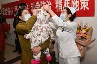2月14日,护士长王颖(右)在出门前帮奇奇(化名)戴好帽子。新华社发(彭子洋 摄)