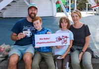 """2月15日,在新西兰首都惠灵顿东方湾海滨,一家人手持用英语和毛利语写的""""抗击疫情!中国加油!""""字样的牌子,声援中国抗击疫情。"""