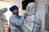 2月18日,在江西中医药大学附属医院抚生院区更衣室内,交班的护士协助即将进入隔离病区的同事穿好防护服。