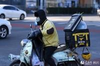 2月17日,一名外卖员正在送餐路上。(人民网记者 翁奇羽 摄)