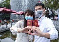 2月14日,完成结婚登记的张铃雯(左)和黄苗炜在深圳市南山区民政局婚姻登记处前合影。