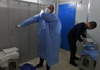 李华(左)和同事在雷神山医院换衣间穿防护服(3月7日摄)。
