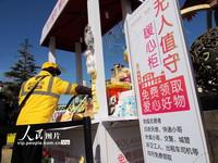 """3月10日,外卖小哥在领取""""无人值守暖心柜""""的物品。"""